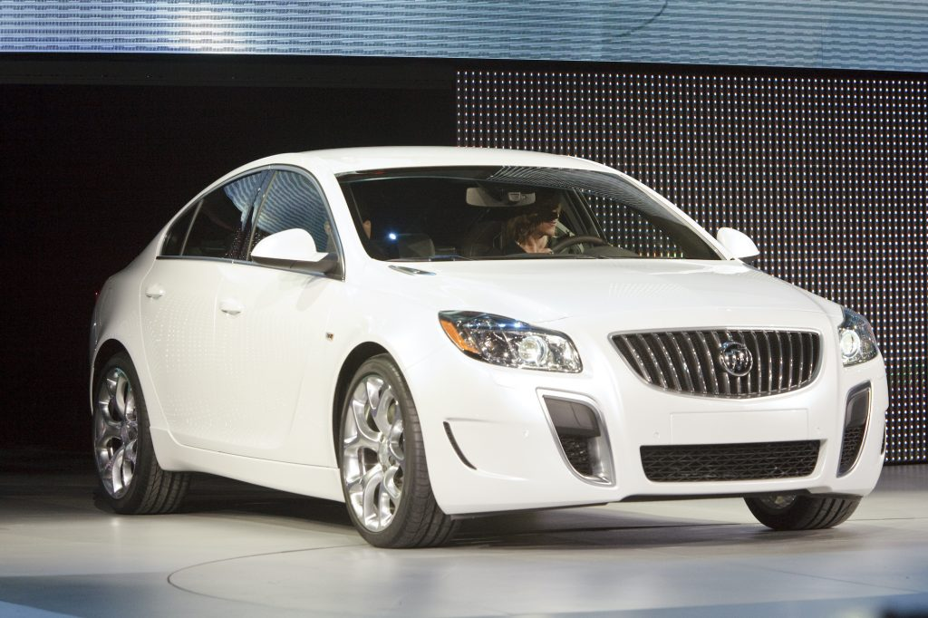 woman drives 2011 Buick Regal on an auto show stage