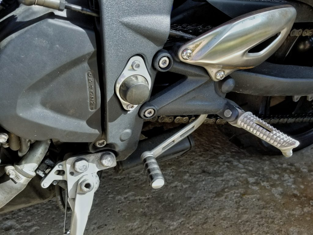 A close-up of the 2012 Triumph Street Triple R's toe shifter and transmission gear position diagram