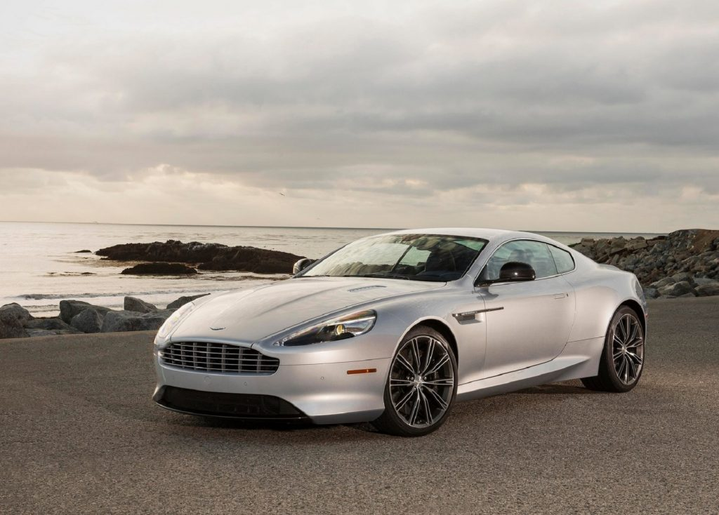 A 2013 Aston Martin DB9 parked in front of a rocky ocean beach