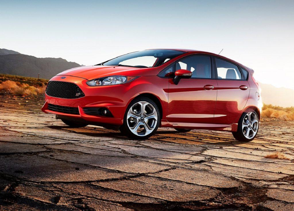 An orange 2014 Ford Fiesta ST parked on desert asphalt