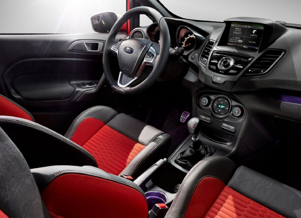 The orange Recaro front seats and black dashboard of a 2014 Ford Fiesta ST