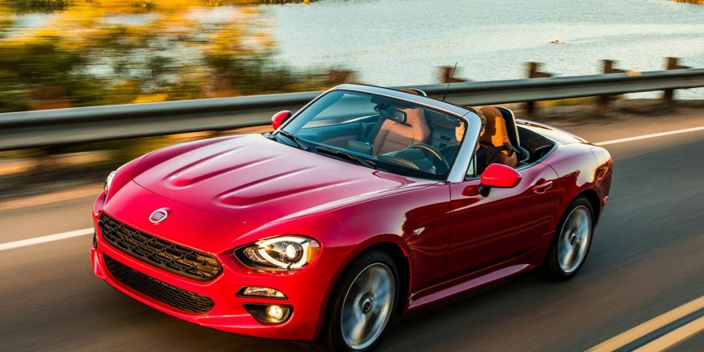 A red 2017 Fiat 124 spider with the top down on the highway.