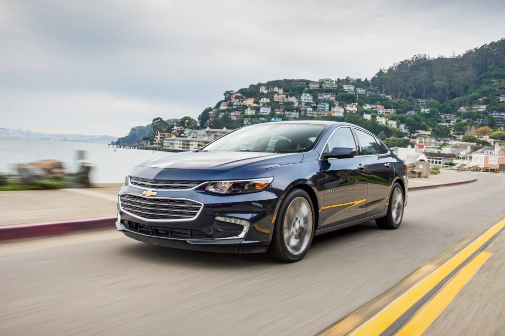 The 2018 Chevy Malibu driving down the road with the ocean and a town in the background.