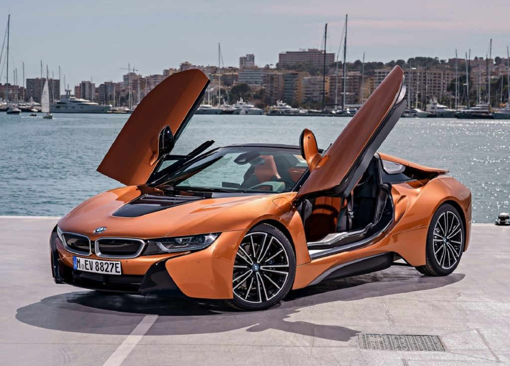 An orange 2019 BMW i8 Roadster with its roof down and doors up by a harbor
