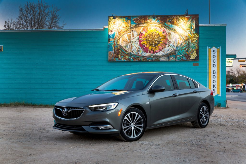 A 2019 Buick Regal Sportback on display in front a blue wall with art hanging above it