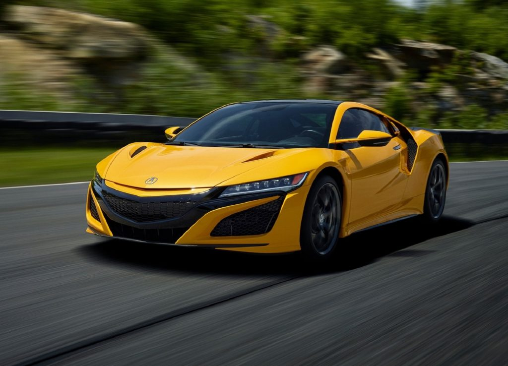 A yellow 2020 Acura NSX drives on a racetrack
