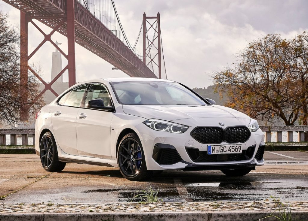 A white 2020 BMW M235i xDrive Gran Coupe in front of a bridge