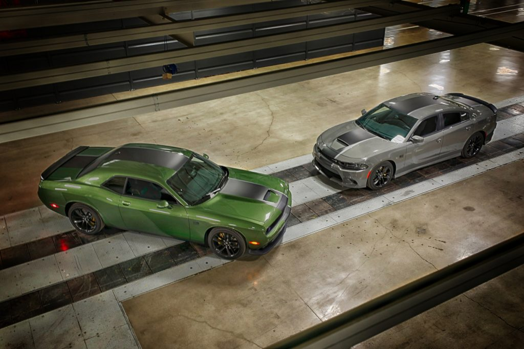 A green 2020 Dodge Challenger on display next to a silver 2020 Dodge Charger
