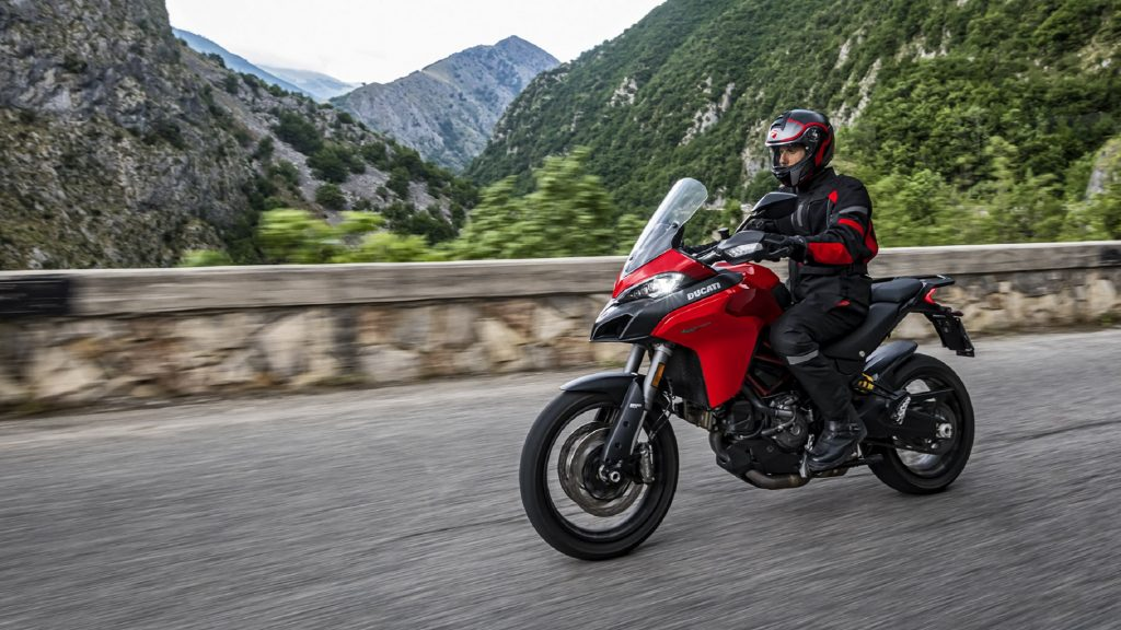 A rider on a red 2020 Ducati Multistrada 950 rides on a mountain road