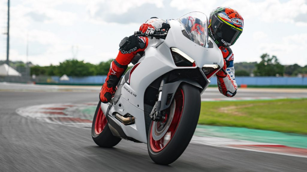 A red-clad rider takes a white 2020 Ducati Panigale V2 on a racetrack