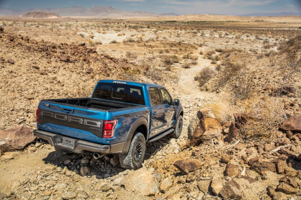 Blue Ford F-150 Raptor pickup driving on gravel desert road