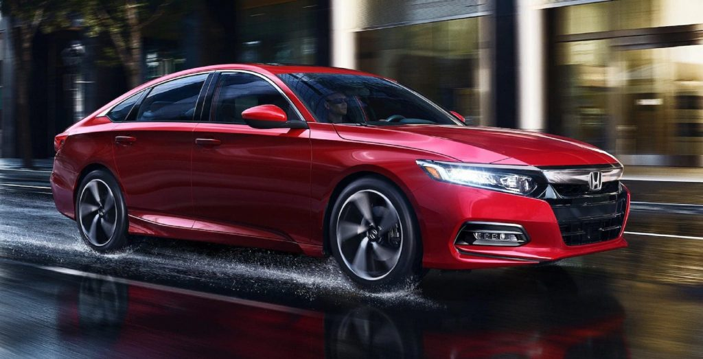 A red 2020 Honda Accord Sport 2.0T drives through a rainy city