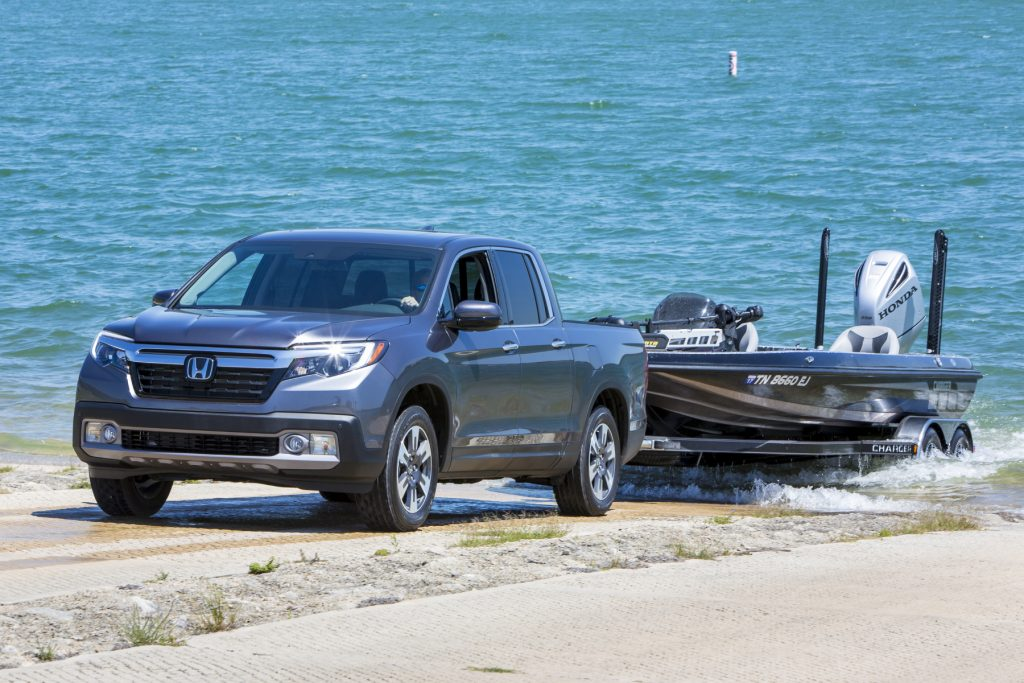 A 2020 Honda Ridgeline towing a small boat near the water