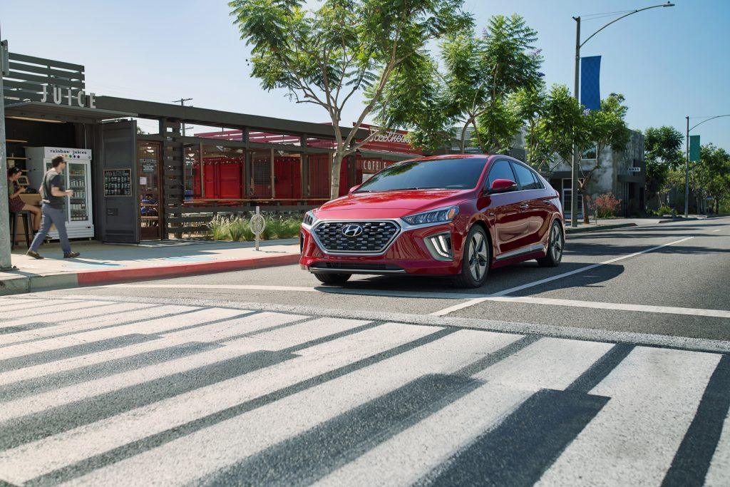 A red 2020 Hyundai Ioniq Hybrid shows off its commuter car capability while stopped at an intersection