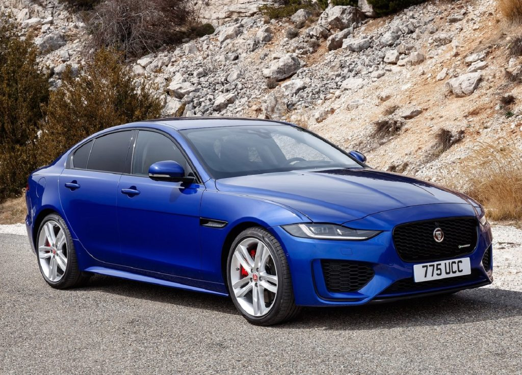 A blue 2020 Jaguar XE in front of a rocky hill