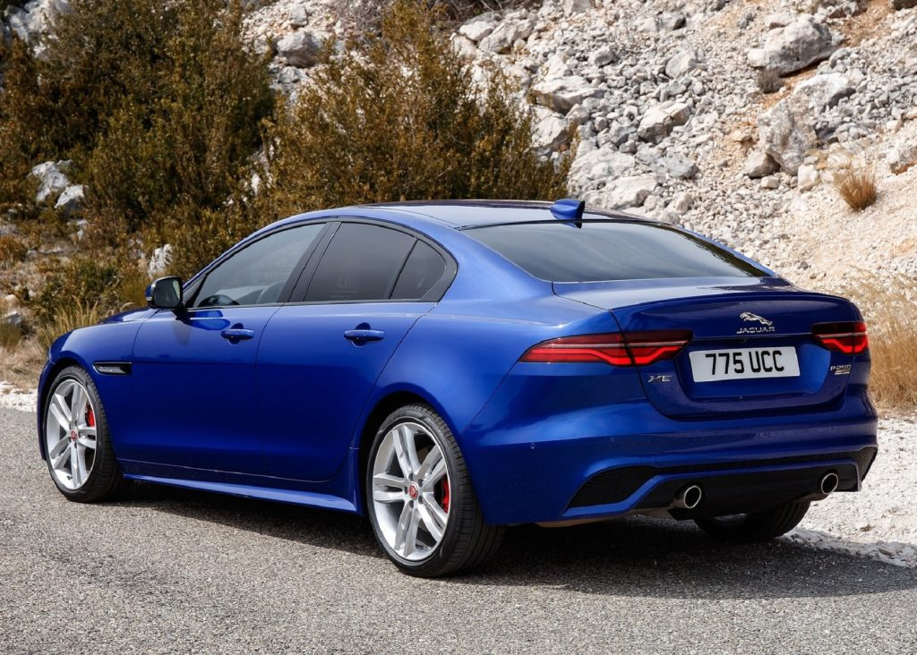 The rear view of a blue 2020 Jaguar XE P250 by a rocky hill