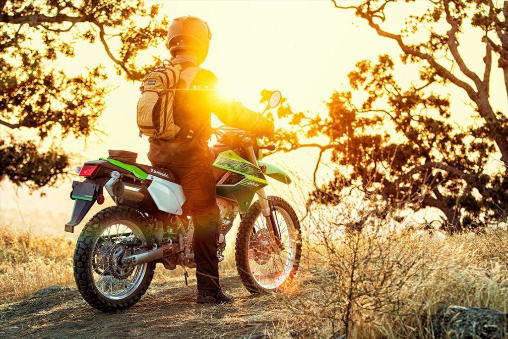 A rider on a green 2020 Kawasaki KLX250 looks at a sunrise