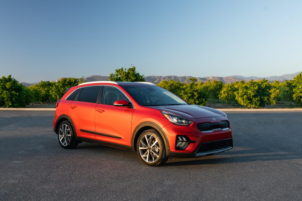 An orange 2020 Kia Niro on display in a parking lot with trees in the background