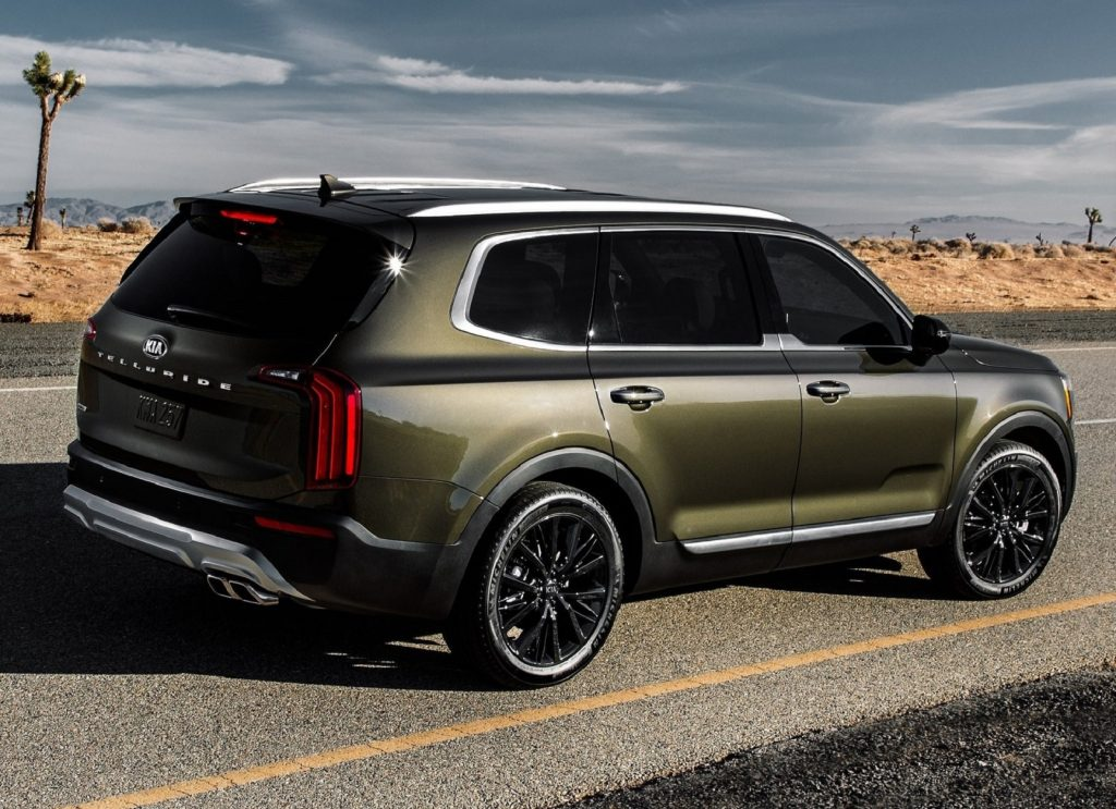 The rear 3/4 view of a green 2020 Kia Telluride on a desert road