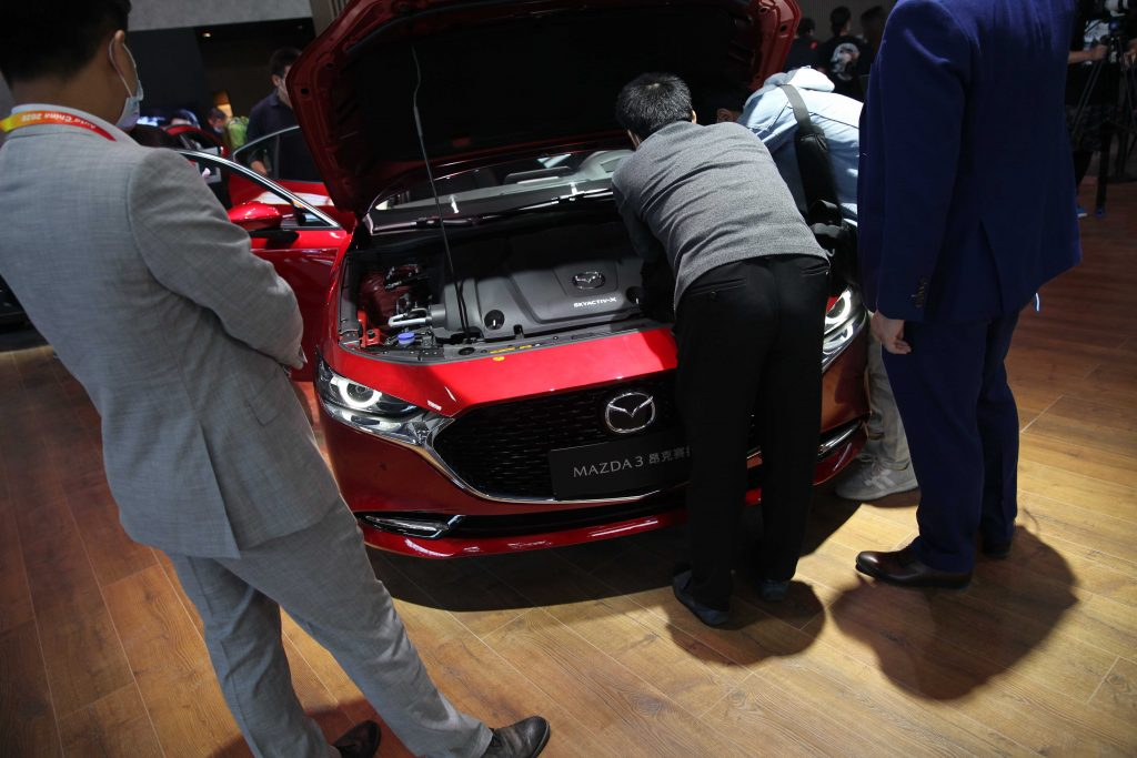 People checking out a Mazda3 at an auto show