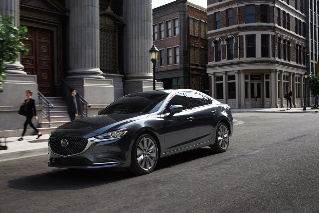 The 2020 Mazda6 driving down a city street with buildings in the background
