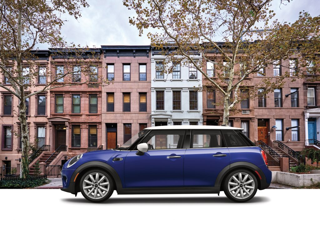A blue 2020 Mini Cooper Oxford Edition on display in front of a building