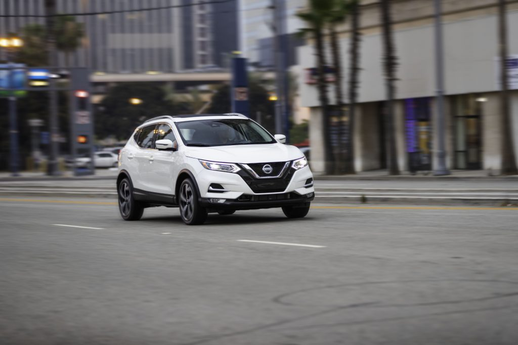 A white 2020 Nissan Rogue Sport driving down a city street, displaying its versatility as a commuter car