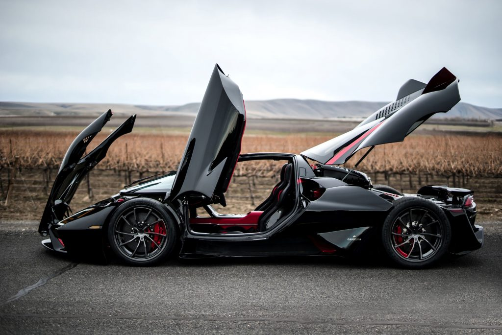 The side view of a black-and-red 2020 SSC Tuatara in the plains with its doors and cover panels up