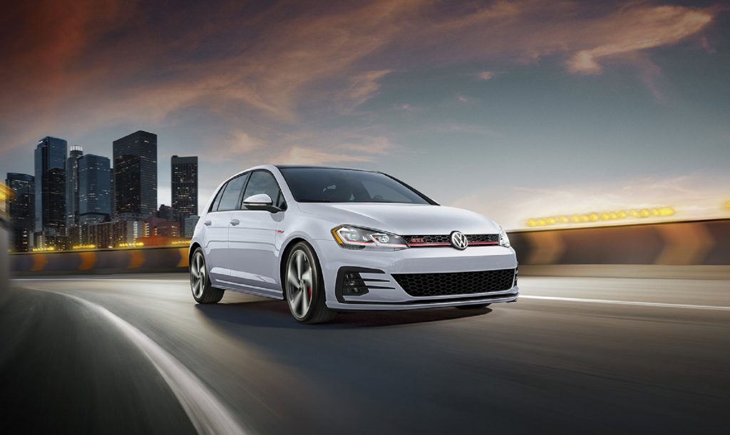 A white 2020 Volkswagen Golf GTI Autobahn drives down the road