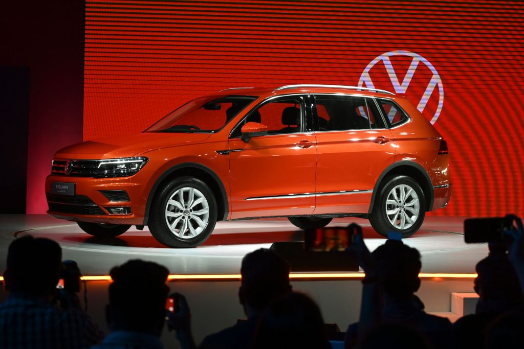 The 2020 Volkswagen Tiguan on display at an auto show with the VW logo in the background