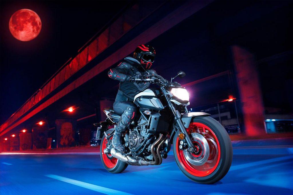 A black-clad rider rides a white 2020 Yamaha MT-07 through a stylized night cityscape