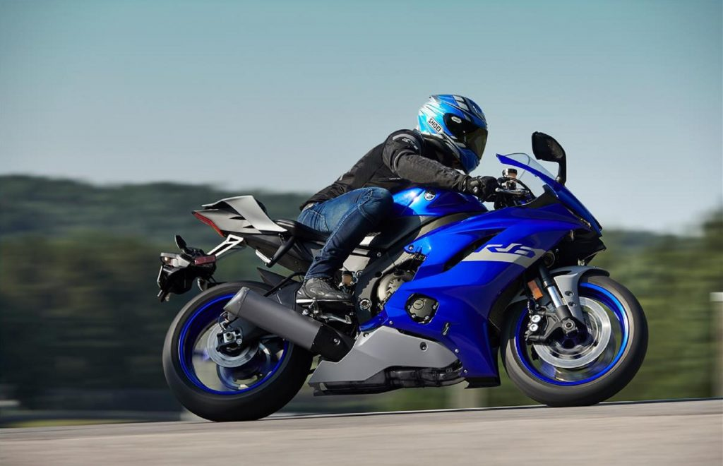 A rider takes a blue 2020 Yamaha YZF-R6 around a track