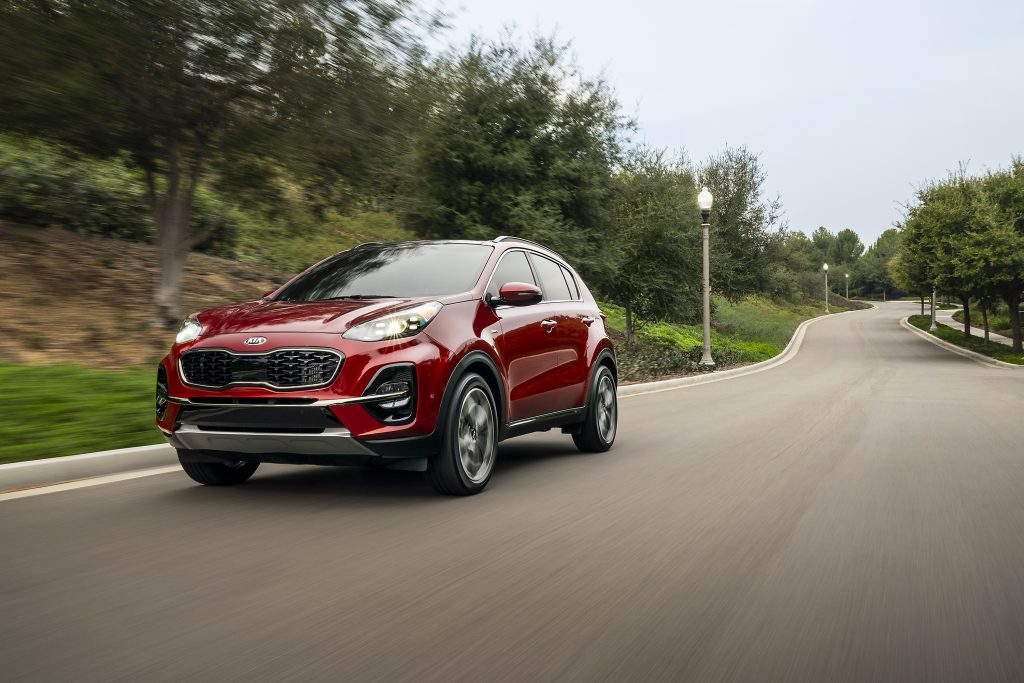 Red 2020 Kia Sportage driving on a road