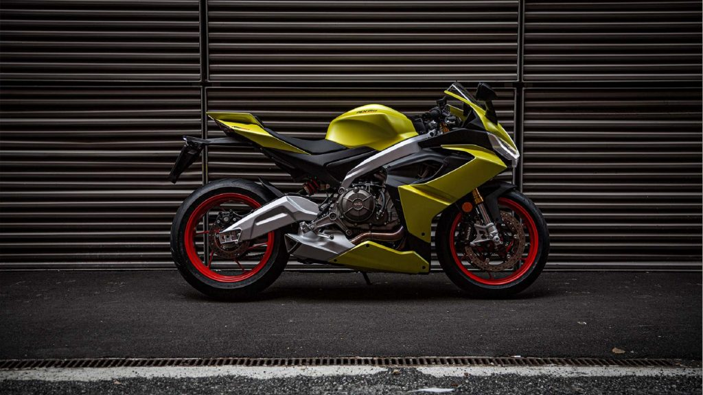 The side view of a bright-yellow 2021 Aprilia RS 660 in front of a garage door