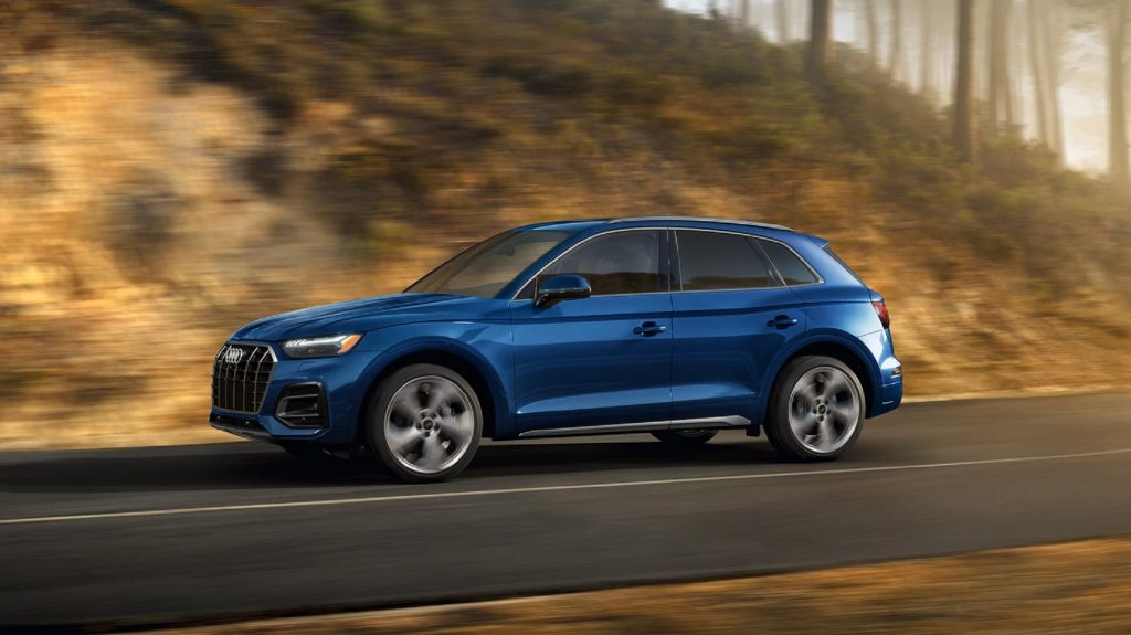 a blue Audi Q5 at speed on a scenic rural road
