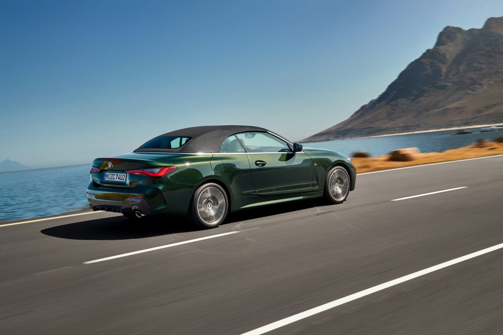 The 2021 BMW 4 Series Convertible driving on a road with an ocean view