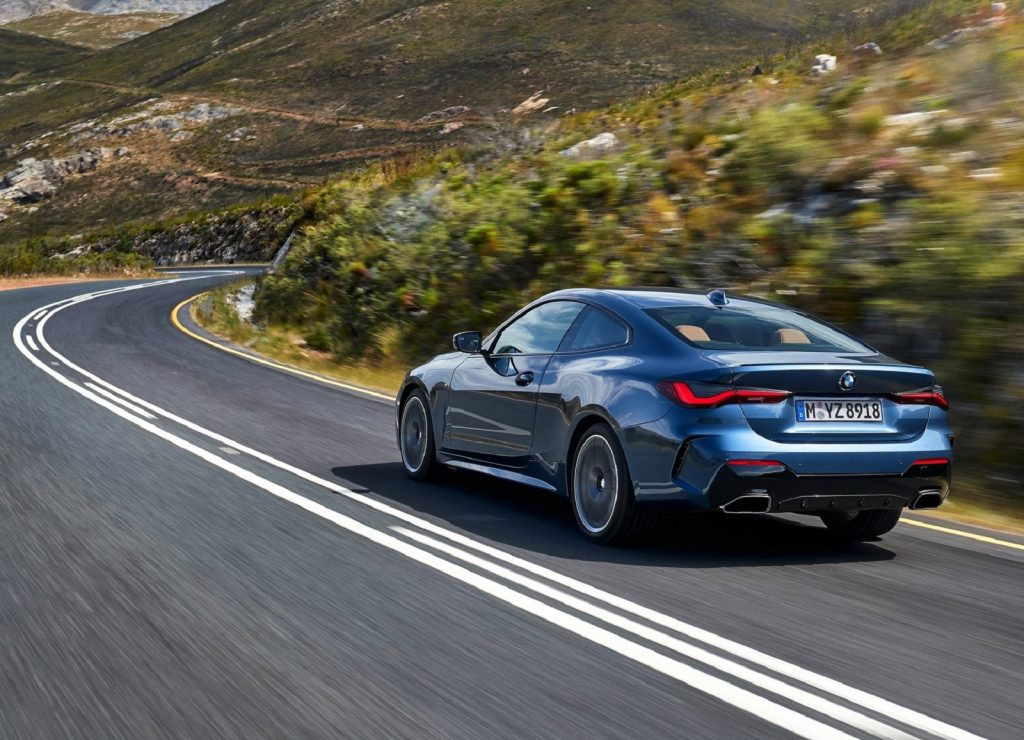 The rear view of a blue 2021 BMW M440i xDrive driving on a highland road