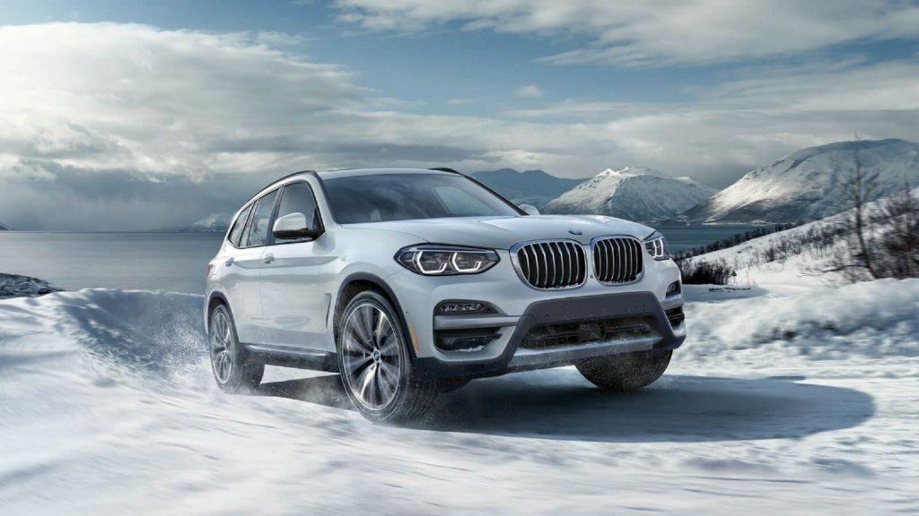 A white 2021 BMW X3 xDrive30e on a snowy mountain