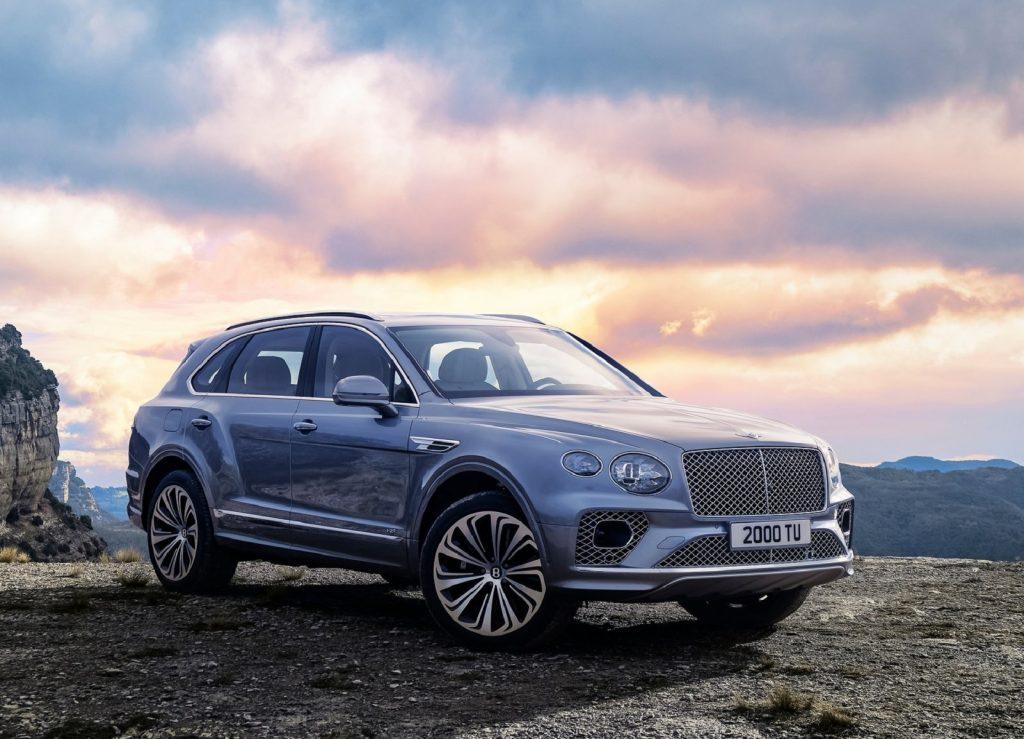 A light-blue 2021 Bentley Bentayga parked next to a rocky cliff
