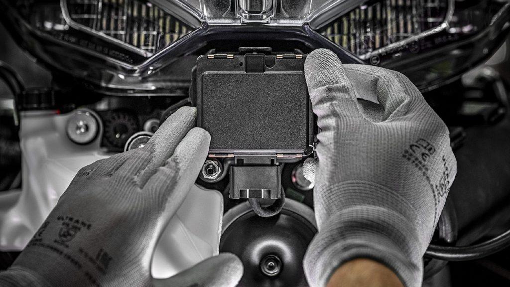 Gray-gloved hands install a radar unit on a 2021 Ducati Multistrada V4