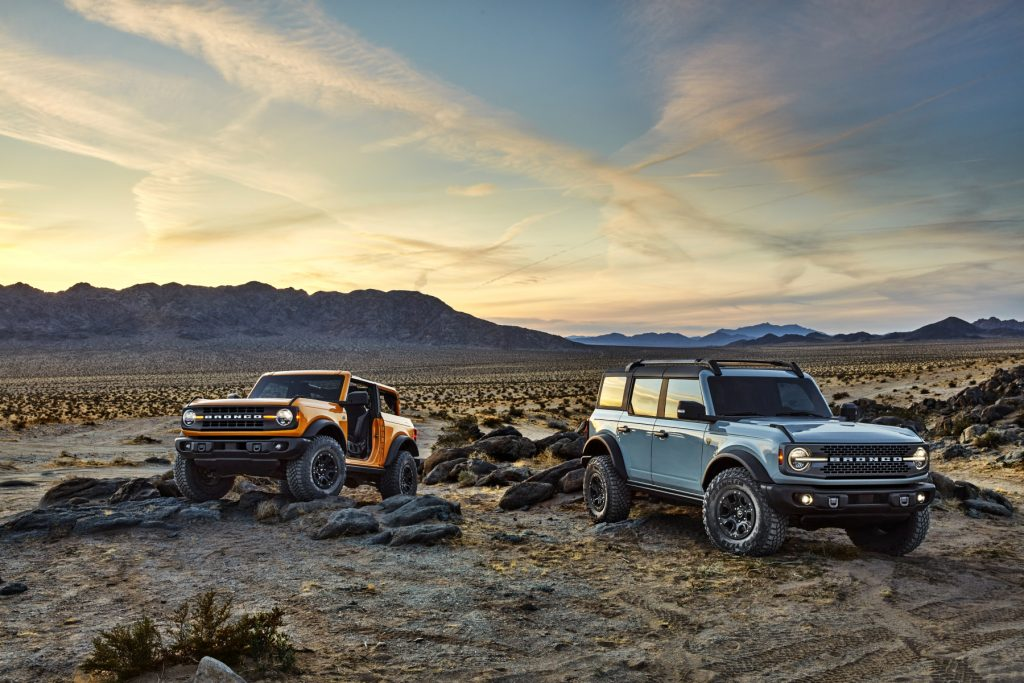 A pair of 2021 Ford Bronco SUVs parked on display over rugged terrain. One is a two-door model, and the other is a four-door model.