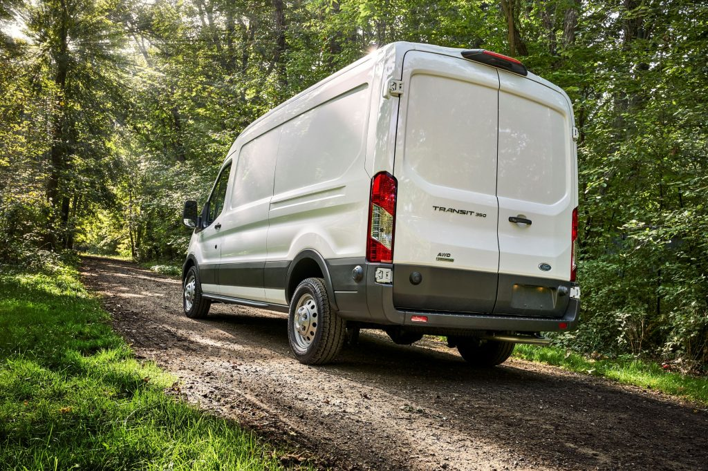 A white 2021 Ford Transit AWD with the Adventure Prep Package drives up a forest hill