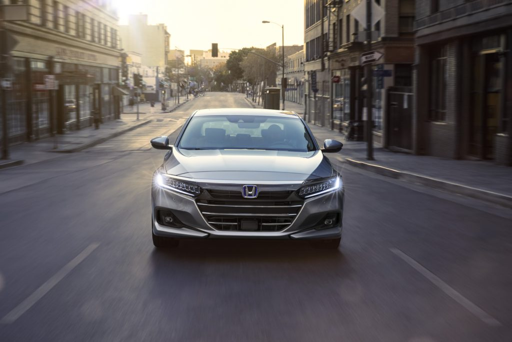 A 2021 Honda Accord Hybrid driving down a city street