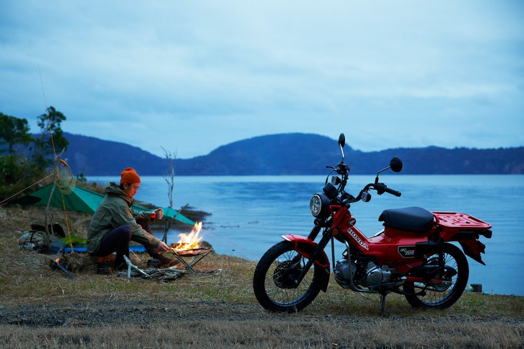 A red 2021 Honda Trail125 ABS by a lake and a campsite