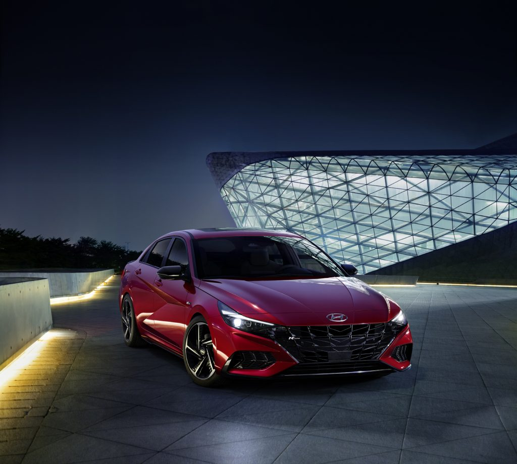 A red 2021 Hyundai Elantra N Line on display in front of a building