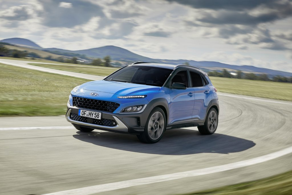 The 2022 Hyundai Kona driving around a curve of a road