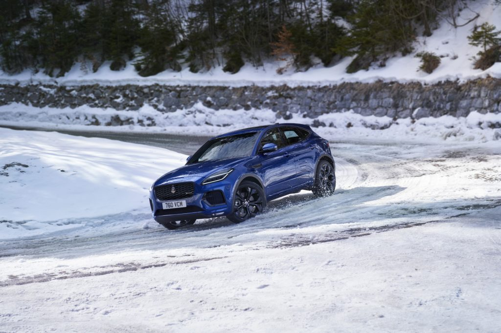 A blue 2021 Jaguar E-Pace driving on a snow-covered road.