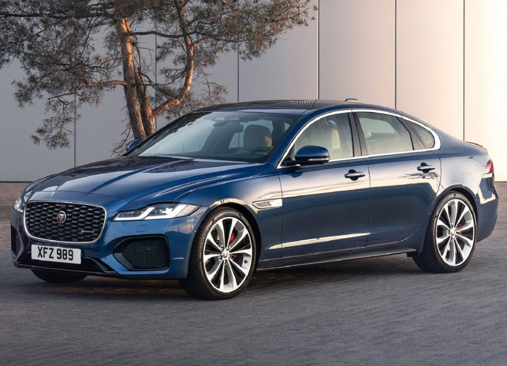 A blue 2021 Jaguar XF in front of a white building