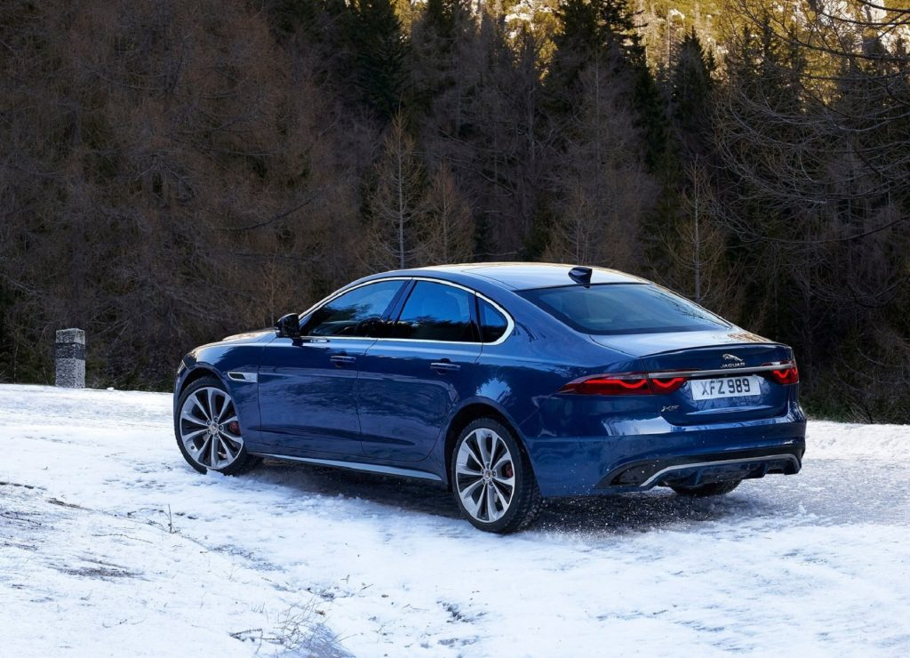 The rear 3/4 view of a blue 2021 Jaguar XF parked on a snowy forest hill