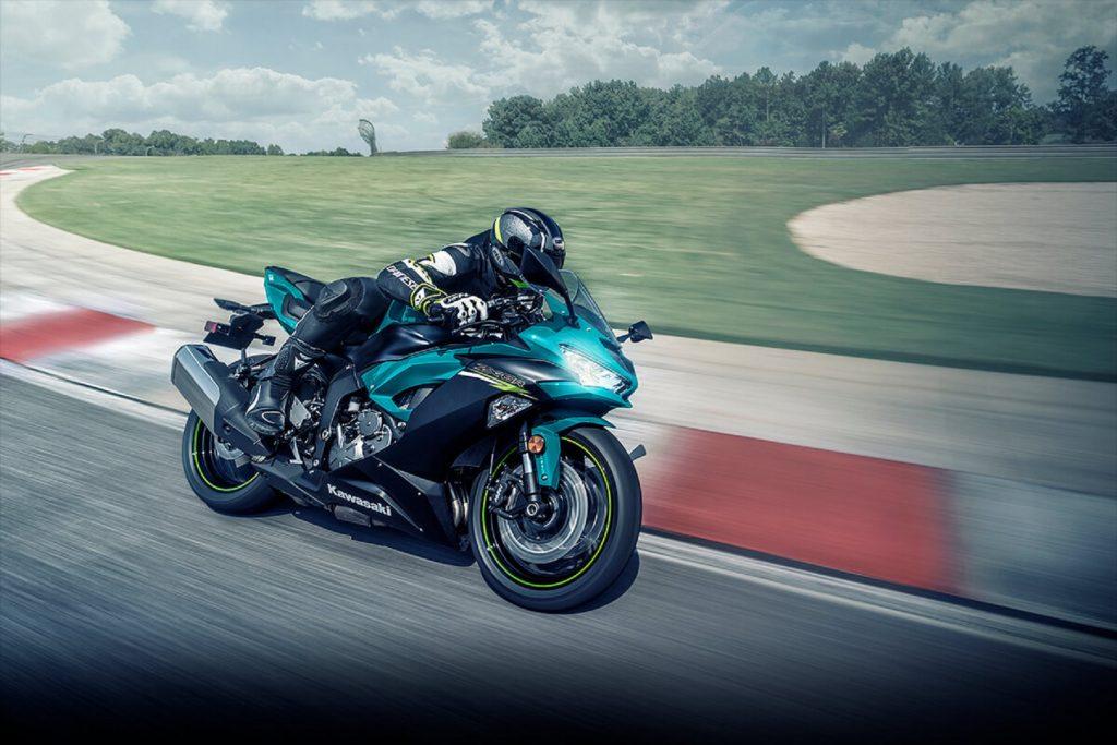 A rider takes a turquoise 2021 Kawasaki Ninja ZX-6R around a track